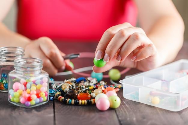 Mulher projetando colar colorido com miçangas plactic