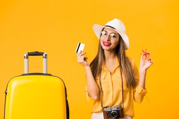 Mulher pronta para a viagem posando com cartão de crédito e bagagem