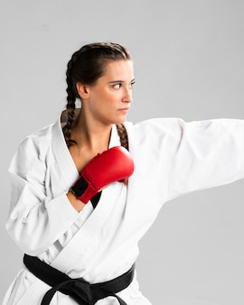 Mulher pronta para lutar com luvas de caixa em fundo branco