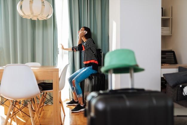 Mulher pronta para viajar, chamando um táxi