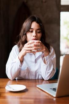Mulher proprietária de café bebendo café
