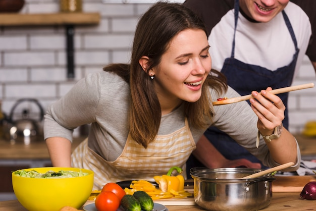 Mulher, provando, alimento, enquanto, cozinhar, com, namorado