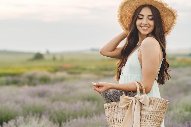 Mulher provençal relaxante no campo de lavanda. senhora com um chapéu de palha. menina com bolsa.