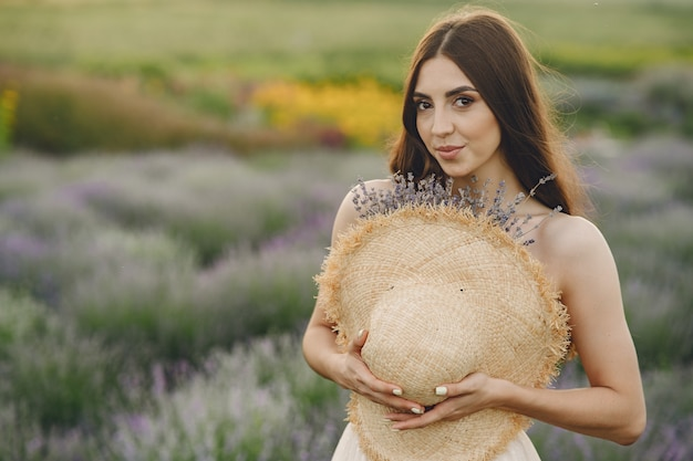 Mulher provençal relaxante no campo de lavanda. senhora com um chapéu de palha.