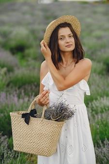 Mulher provençal relaxante no campo de lavanda. senhora de vestido branco. menina com bolsa.