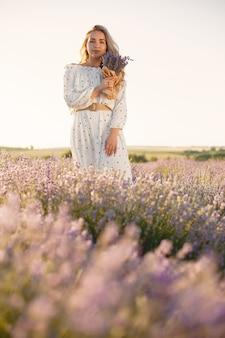 Mulher provençal relaxante no campo de lavanda. senhora de vestido branco. menina com bouquete de flores.