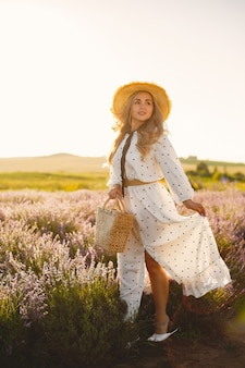 Mulher provençal relaxante no campo de lavanda. senhora de vestido branco. menina com um chapéu de palha e uma cesta.