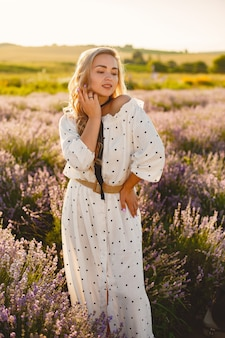 Mulher provençal relaxante no campo de lavanda. senhora de vestido branco. menina com um chapéu de palha.