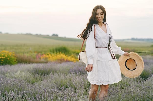 Mulher provençal relaxante no campo de lavanda. senhora de vestido branco.