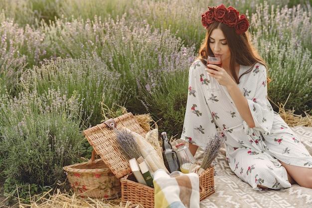 Mulher provençal relaxante no campo de lavanda. senhora em um piquenique. mulher em uma coroa de flores.