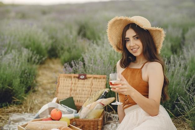 Mulher provençal relaxante no campo de lavanda. senhora em um piquenique.