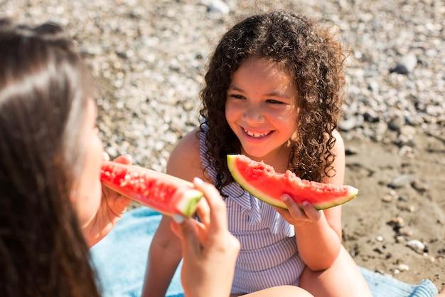 Mulher próxima e criança comendo melancia