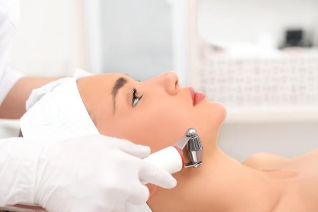 Mulher próxima recebendo massagem facial elétrica no equipamento de microdermoabrasão no salão de beleza.