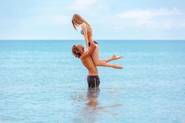 Mulher pula para o homem em seus braços, em pé no mar. ambos estão em trajes de banho. sorrindo brincalhão casal jovem apaixonado se divertindo na praia.