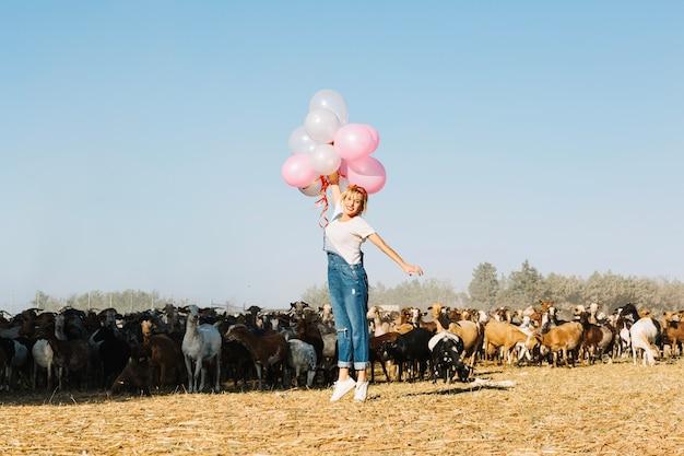 Mulher pulando com balões perto de cabras