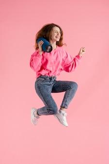 Mulher pulando com bolsas de alto-falante