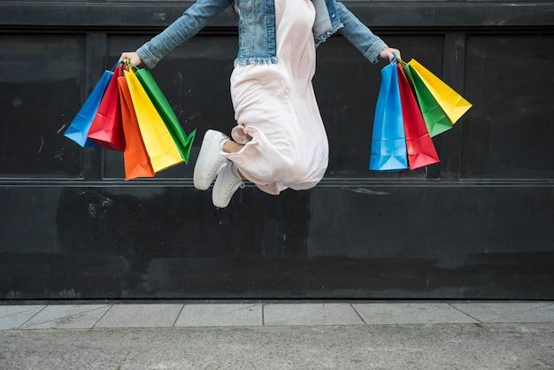 Mulher pulando com pacotes coloridos de compras