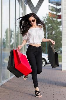 Mulher pulando com sacolas de compras