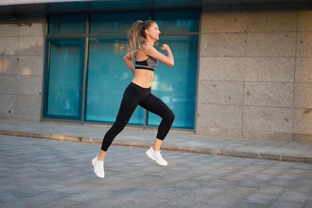 Mulher pulando e correndo contra a superfície urbana da cidade