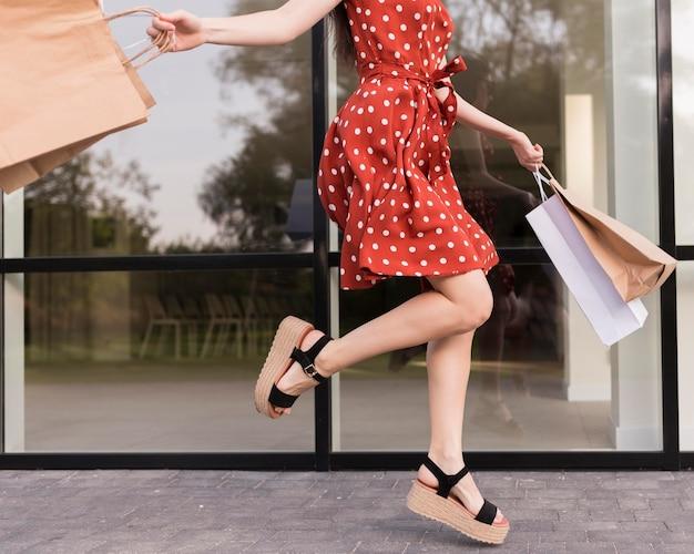 Mulher pulando e segurando sacolas