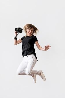 Mulher pulando e segurando uma câmera