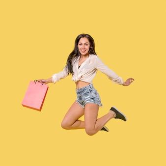 Mulher pulando feliz com saco