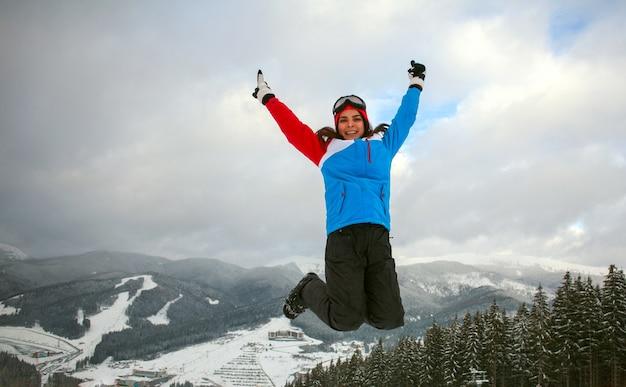 Mulher pulando feliz no inverno na estação de esqui