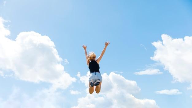 Mulher pulando no fundo do céu azul