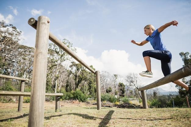 Mulher pulando obstáculos durante a pista de obstáculos no campo de treinamento