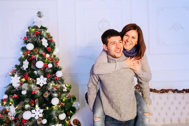 Mulher pulando sobre os ombros do homem na véspera de natal