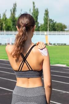 Mulher pulverizando creme protetor solar na pele antes de correr. esportes e conceito saudável.
