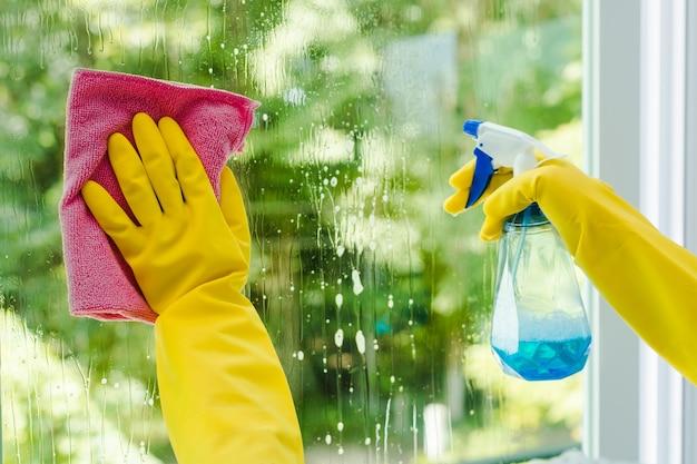 Mulher pulverizando e limpando vidro