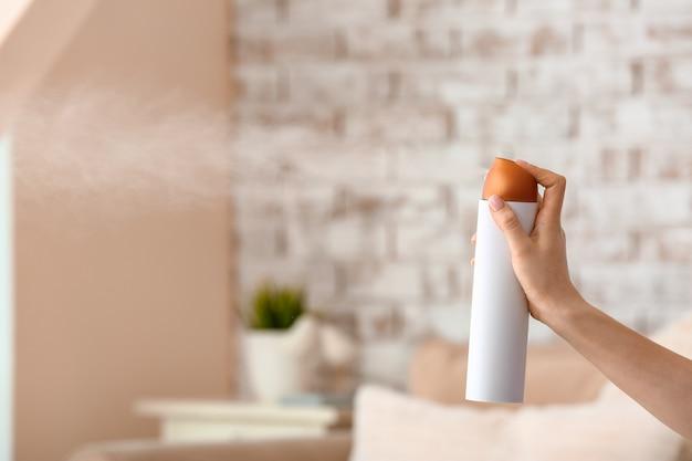 Mulher pulverizando purificador de ar no quarto