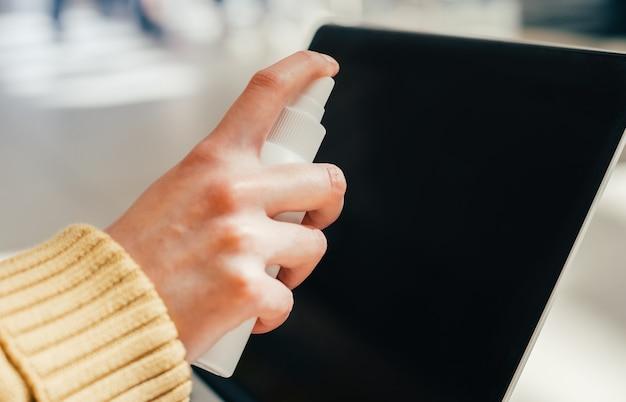 Mulher pulverizando spray na tela do laptop