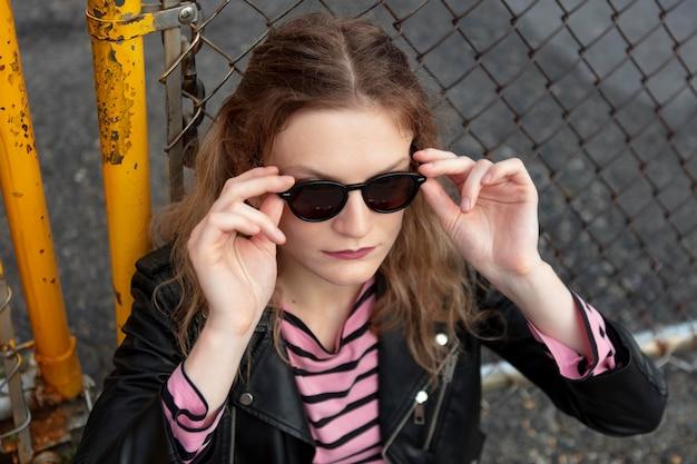 Mulher punk com óculos de sol em local urbano