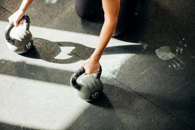 Mulher push-up força flexão exercício em kettlebells em um treino de fitness