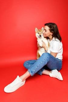 Mulher que abraça, abraçando o cão de shiba inu, isolado no fundo vermelho. amor aos animais