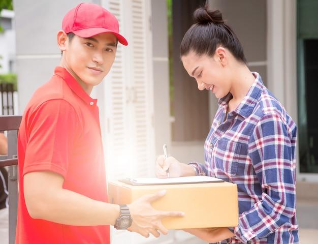 Mulher que aceita uma entrega das caixas do correio do serviço de entrega. isolado em um fundo branco.