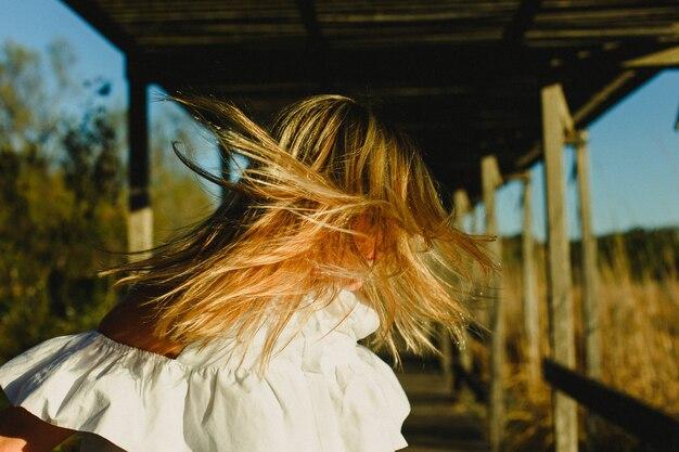 Mulher que agita sua cabeça para acenar seu cabelo longo, fundo das árvores.