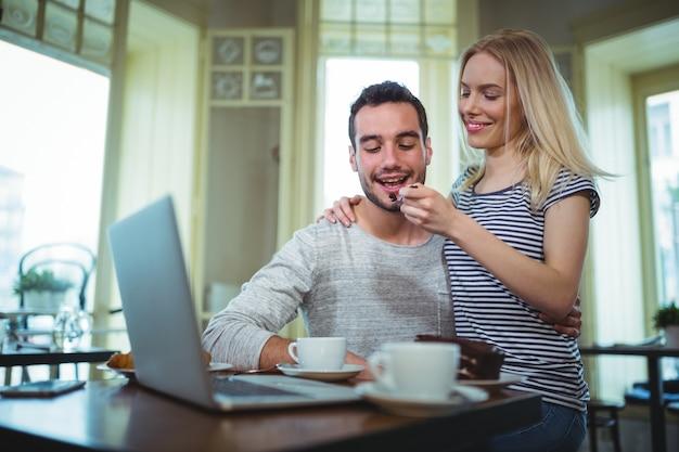 Mulher que alimenta a pastelaria para o homem no cafã ©