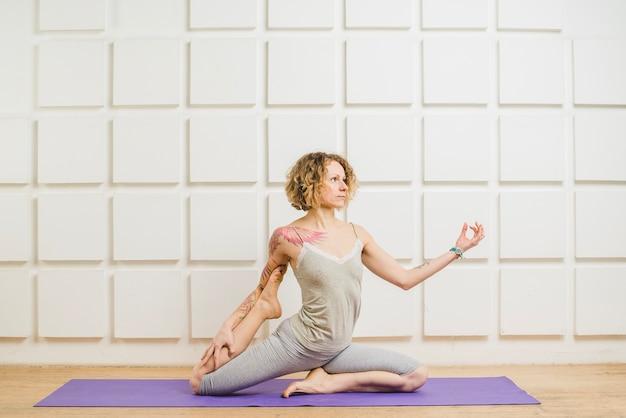 Mulher que alonga a perna e medita