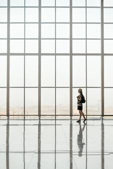 Mulher que anda na frente de uma janela de vidro gigante