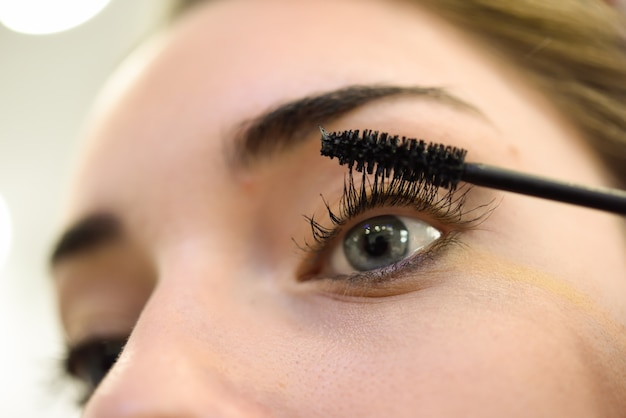 Mulher que aplica cílios maquiagem