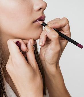 Mulher que aplica delineador de lábios no modelo