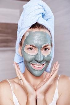 Mulher que aplica o creme de pele hidratando da máscara no rosto que olha no espelho do banheiro. menina cuidando de seu creme hidratante de camadas de pele. tratamento de spa para a pele.