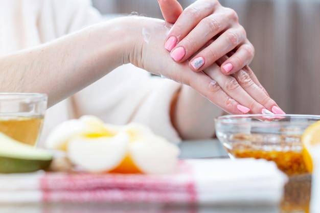 Mulher que aplica o creme em suas mãos que nutre-as com o close-up natural dos cosméticos. higiene e cuidados para a pele