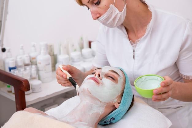 Mulher que aplica uma máscara facial para um cliente