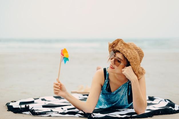 Mulher que aprecia a praia que relaxa alegre no verão pela água azul tropical.