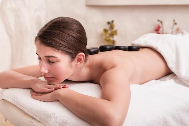 Mulher que aprecia a terapia de rocha no spa