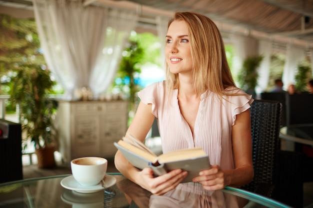 Mulher que aprecia um livro e uma chávena de café